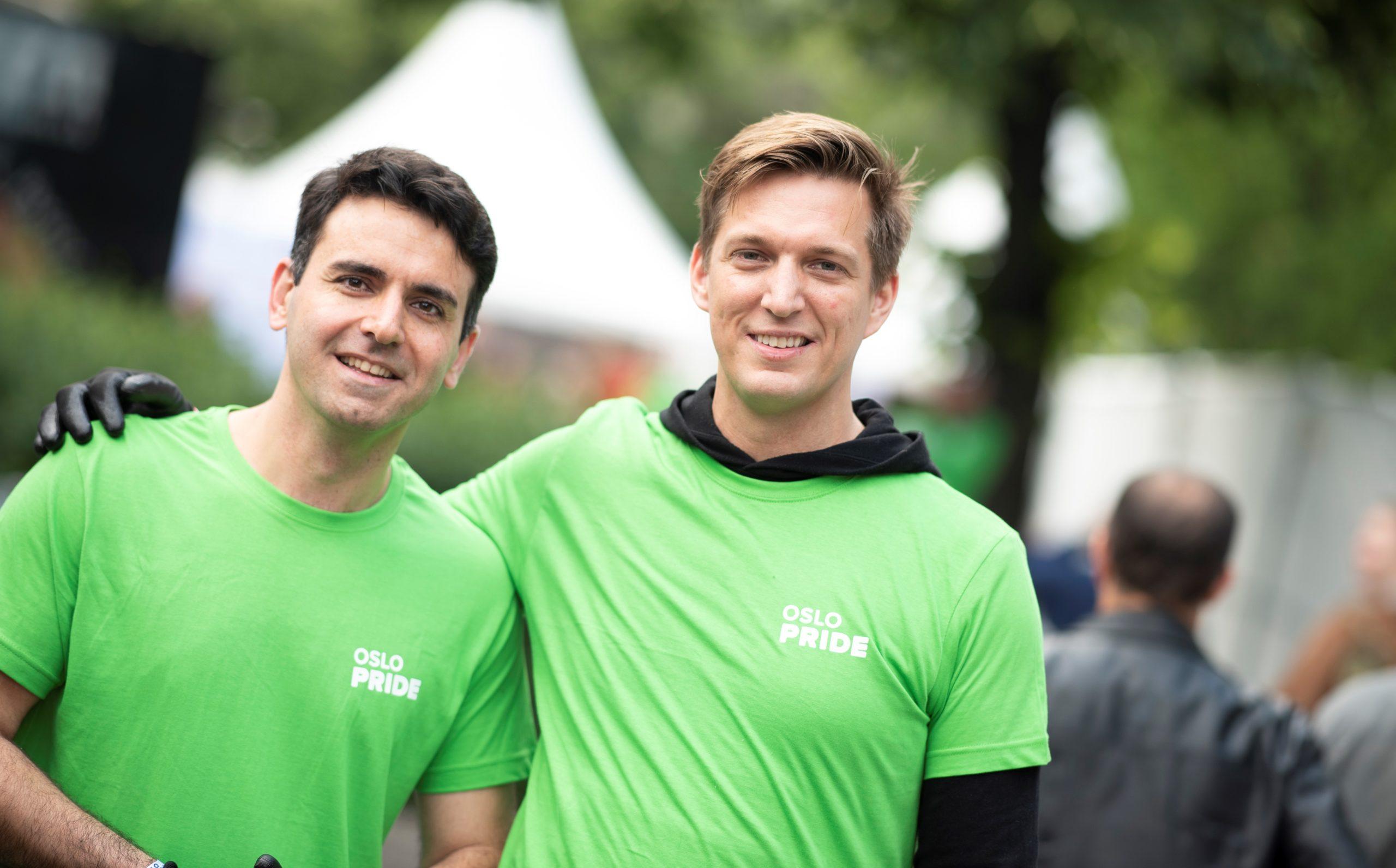 To hvite menn smiler til kamera. De har på seg grønne t-skjorter der det står Oslo Pride med hvit skrift. Den ene holder en arm rundt skulderen til den andre. Begge har sorte arbeidshansker på. De står foran noen hvite telt og sommergrønne trær, som vi skjønner er festivalområdet.