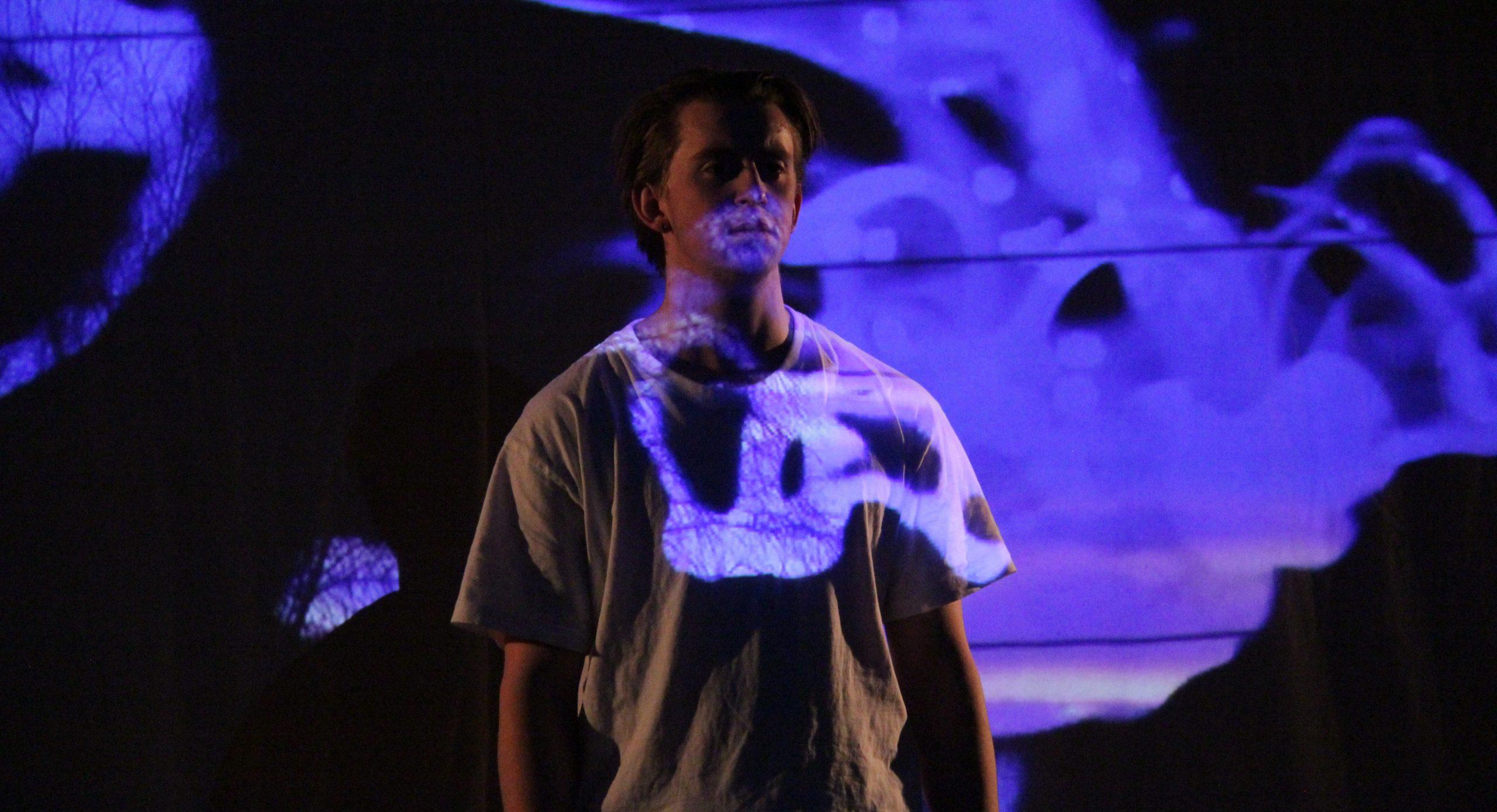 Person står i mørket med blått lys reflketert på deler av overkroppen og bakgrunnen. Vio forstår at hen står på en slags scene.